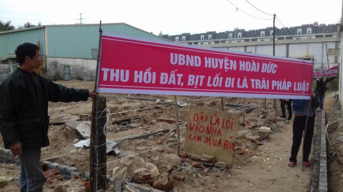Người dân viết biểu ngữ phản đối việc UBND huyện Hoài Đức thu hồi đất, bán đấu giá, bịt lối đi của người dân.