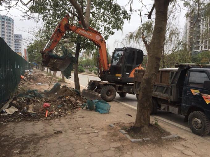 Lực lượng chức năng huy động xe cẩu dọn dẹp phế thải do người dân đổ trộm dọc bờ sông Lừ.