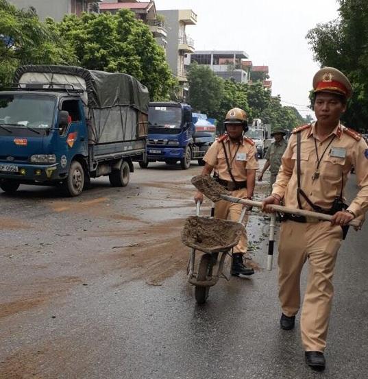 Lực lượng CSGT có mặt tại hiện trường xử lý vết dầu do xe tải làm rơi.