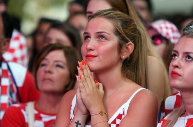 Nữ cổ động viên cầu nguyện trong suốt thời điểm trận đấu diễn ra