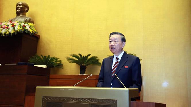 Bộ trưởng Bộ Công an Tô Lâm thừa ủy quyền trình bày báo cáo trước Quốc hội.(Ảnh: Quochoi.vn)