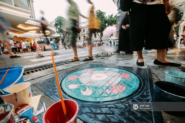 Dù trời mưa nhưng các bạn trẻ vẫn cố gắng hoàn thiện bức tranh.