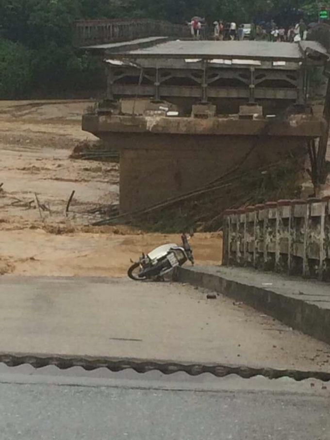 Chiếc xe máy còn vương lại sau khi chiếc cầu bị sập.(Ảnh: Tùng Duy - Báo Tiền Phong)