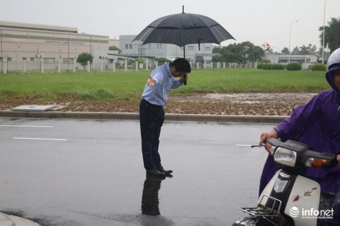 Ông Hiroaki Honjo, Tổng giám đốc Công ty Xăng dầu IQ8 có mặt tại trạm xăng dầu Thăng Long, ông đội mưa hàng tiếng đồng hồ, cúi chào khách vào đổ xăng. (Ảnh: infonet)