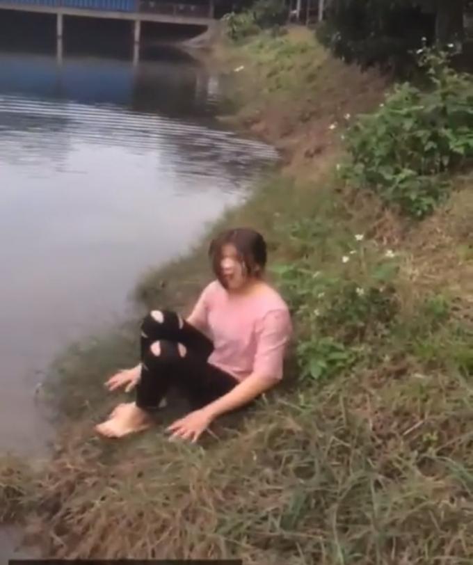 Cô gái ngồi trên bờ run rẩy sau khi ngoi lên bờ - Ảnh cắt từ clip.