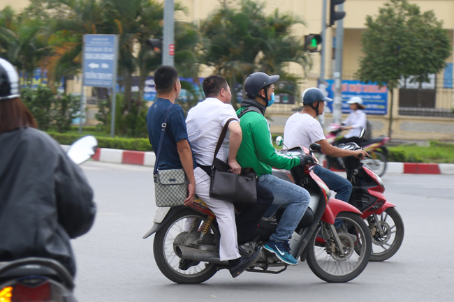 Ở Hà Nội, không khó để bắt gặp hình ảnh tài xế GrabBike kẹp 3, không đội hoặc thiếu mũ bảo hiểm.