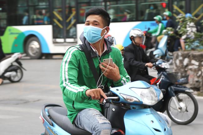 Một tài xế đầu trần, đeo tai nghe, lái xe bằng một tay còn một tay cầm điện thoại rất nguy hiểm trên đường.