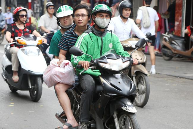 Tài xế GrabBikechở 3 ở phố Hàng Ngang, Hàng Đào, nhiều hành khách còn không có mũ bảo hiểm để đội.