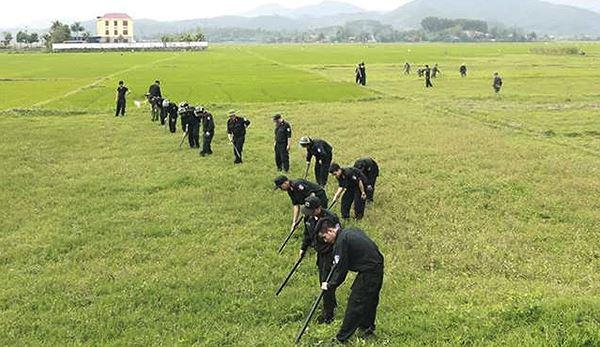 Cảnh sát lật từng bụi cỏ tìm súng và lựu đạn quanh vị trị chiếc xe các đối tượng cố thủ