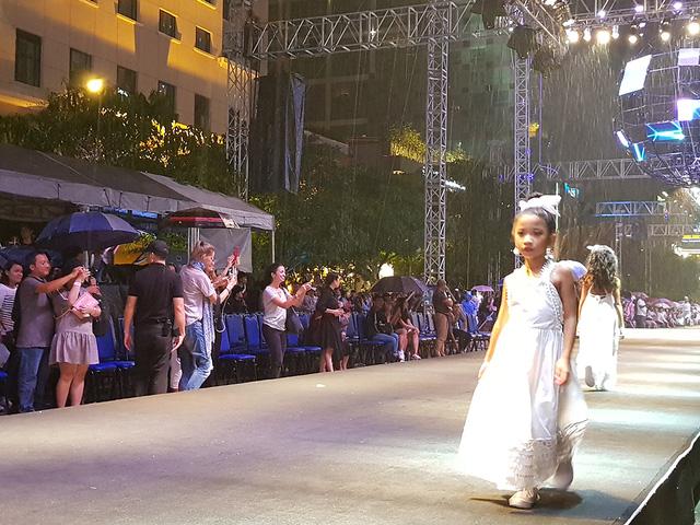 Các người mẫu nhí cũng vô cùng chuyên nghiệp khi tiếp tục hoàn thành phần trình diễn trên sàn catwalk dài 120m của chương trình, mặc cho mưa ngày càng lớn hơn.