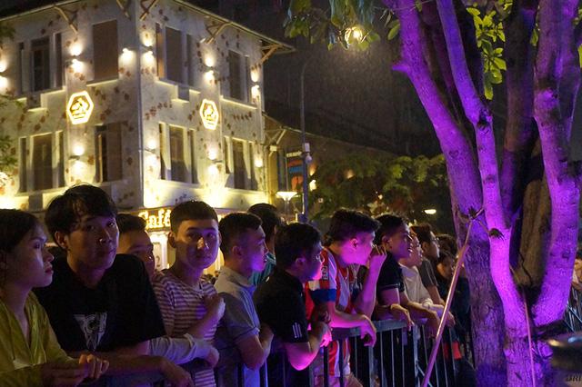 Phía ngoài hàng rào của khu vực biểu diễn, các khán giả vẫn tiếp tục hướng mắt về sân khấu để theo dõi chương trình.