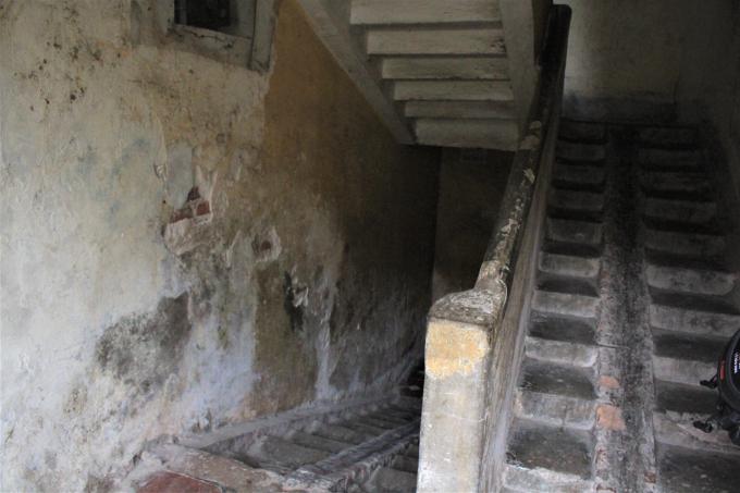 Cầu thang loang lổ những mảng tường nứt vỡ, trơ gạch.