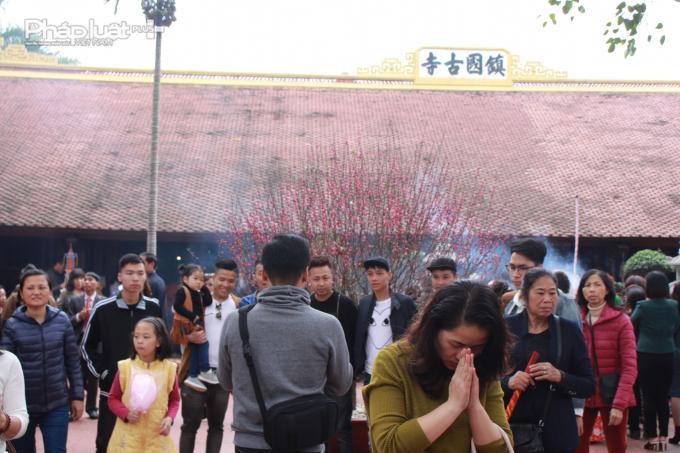 Nhiều người cầm theo hương, sớ... khi thắp hương, khấn vái khắp khu vực sân chùa.