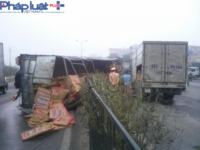 Hàng hóa trong xe tải đổ tràn lan ra đường.