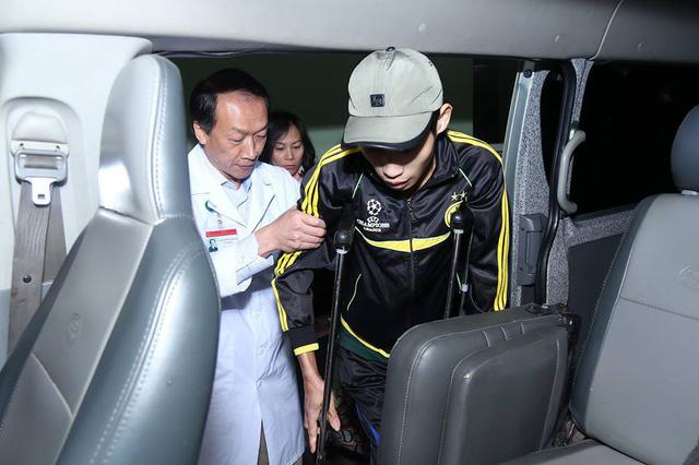 Ông ân cần dìu một thanh niên trẻ phải chống nạng lên xe.