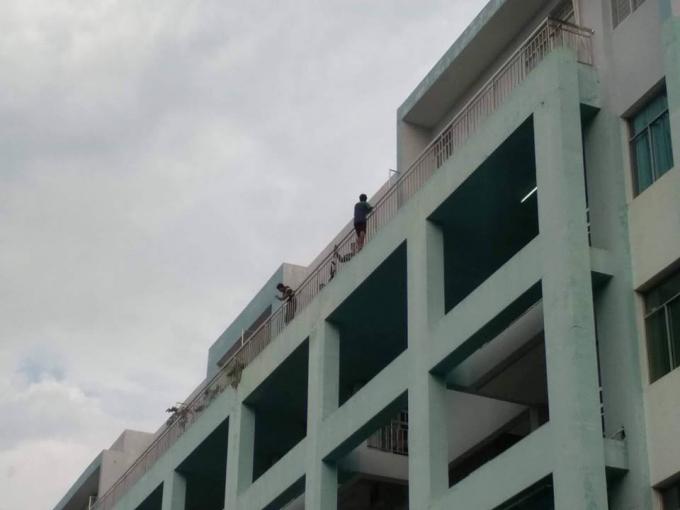 Thanh niên này đang trèo ra lan can bệnh viện đòi nhảy lầu nếu bạn gái không đến.
