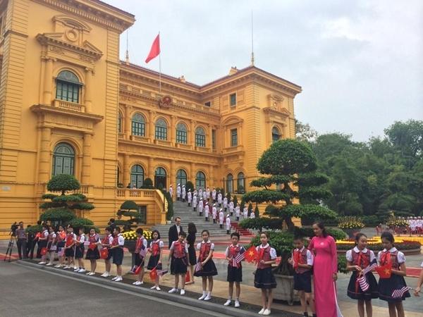 Các em học sinh cầm cờ hoa chuẩn bị chào đón Tổng thống Mỹ Barack Obama. (Vnexpress)
