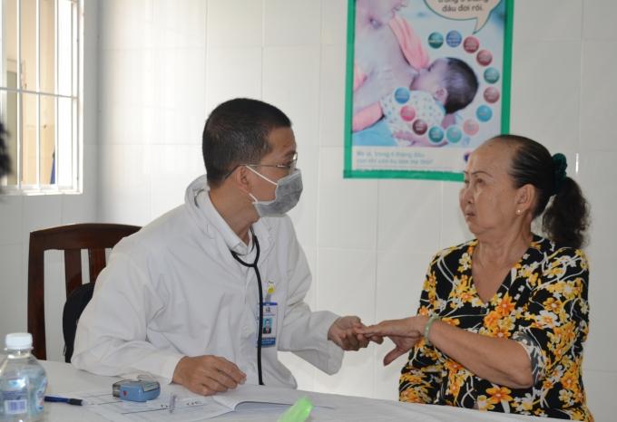 Các bác sĩ tận tình giúp đỡ một cụ già neo đơn vào khám bệnh.