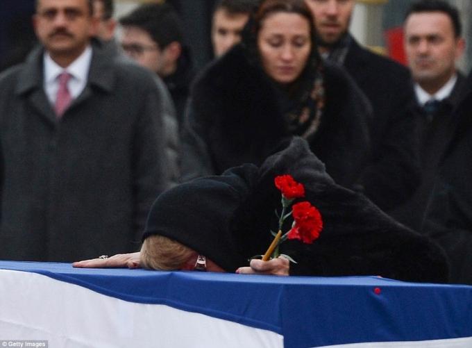 Tại lễ tưởng niệm ông Karlov tại sân bay Esenboga trước khi trở về Nga, bà Marina tay cầm hai bông hoa cẩm chướng đỏ gục đầu khóc bên quan tài phủ quốc kỳ của chồng. (Ảnh:Getty)