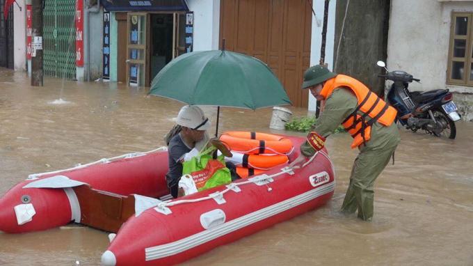 Lực lượng chức năng dùng xuồng phao đưa người dân vùng bị ngập nước đến nơi an toàn.'