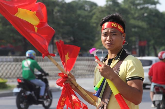 Một nam thanh niên nhiệt tính mời khách mua cờ, kèn cổ vụ cho đội tuyển Việt Nam.