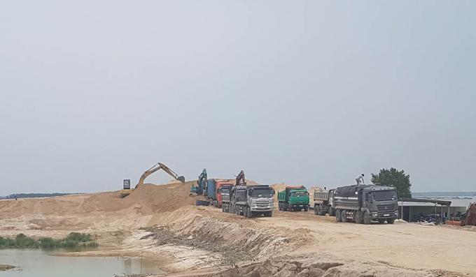 Xe chở cát cỡ lớn có nối đuôi nhau hoạt động tại bãi cát trong lòng hồ Dầu Tiếng.