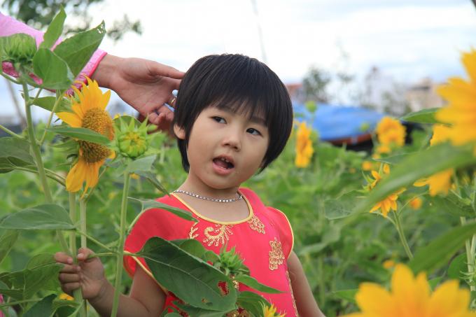 Cháu bé thích thú tạo dáng chụp hình trong vườn hoa.