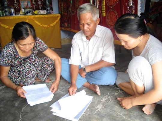 Gia đình ông Huỳnh Chiếm Lạc với tập hồ sơ khởi kiện. Ảnh. NLD