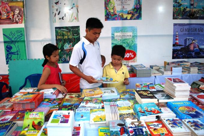 Người cha cẩn thận lựa chọn cho hai người con của mình những cuốn sách phù hợp, ưng ý nhất.