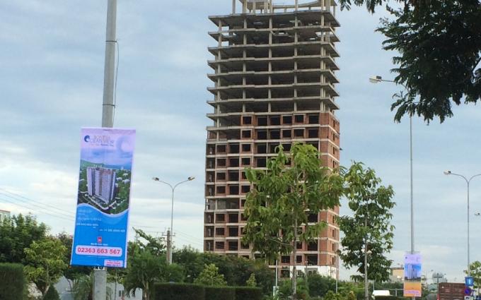 Tòa nhà thuộc dự án The Summit bị bỏ không 7 năm,nằm bên băng rôn cái tên mới Sơn Trà Ocean View mà công ty địa ốc Minh Trần đang treo rao bán dự án ngay trục Ngô Quyền - Đinh Công Trứ.