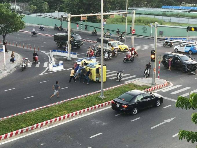 Người dân hợp lực đẩy chiếc xe taxi bị lật ngửa để giúp tài xế thoát ra ngoài. Ảnh:FB Bách Khoa.