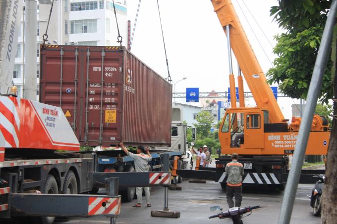 Cơ quan chức năng nâng container lên xe sau vụ tai nạn giao thông.