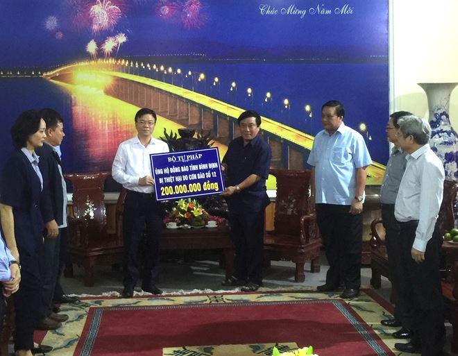 Bộ trưởng Lê Thành Long trao 200 triệu đồng, số tiền mà cán bộ, công chức Bộ Tư pháp ủng hộ nhân dân vùng lũ tỉnh Bình Định.