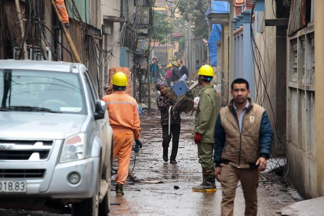 Chiều 4/1, khắp đường làng, ngõ xóm gần nơi phát nổ vẫn ngổn ngang đất đá, vật liệu, người dân tất bật dọn dẹp để ổn định lại sinh hoạt.