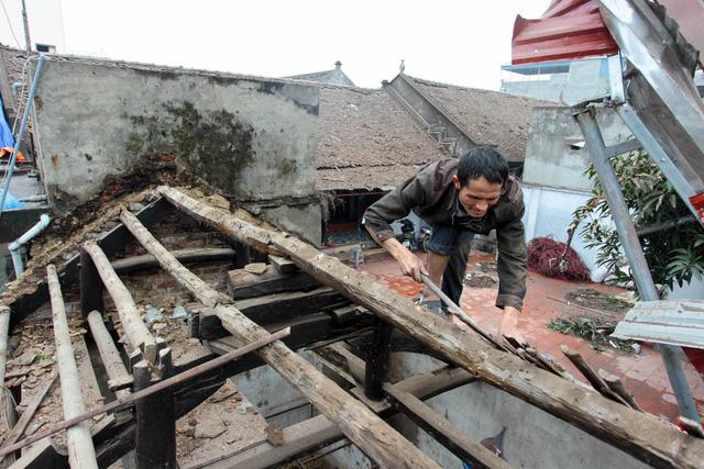 Một gia đình ở thôn Quan Độ đang sửa lại mái nhà đã bị sức ép của vụ nổ thổi bay toàn bộ ngói lợp.