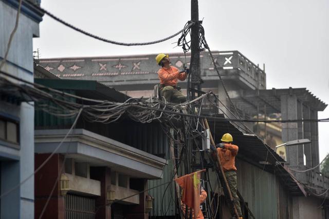 Nhiều cột điện gãy đổ sau vụ nổ. Trong cả ngày 4/1, thợ điện hối hả khôi phục để sớm cấp điện trở lại cho người dân.