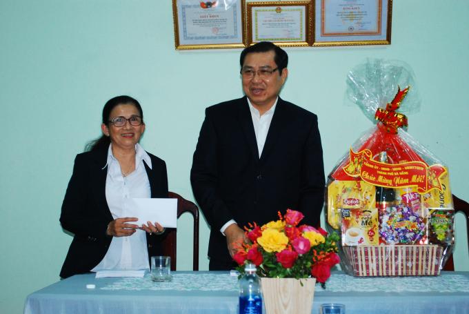 Lãnh đạo Trung tâm nuôi trẻ mồ côi (trái) nhận quà động viên của lãnh đạo thành phố.
