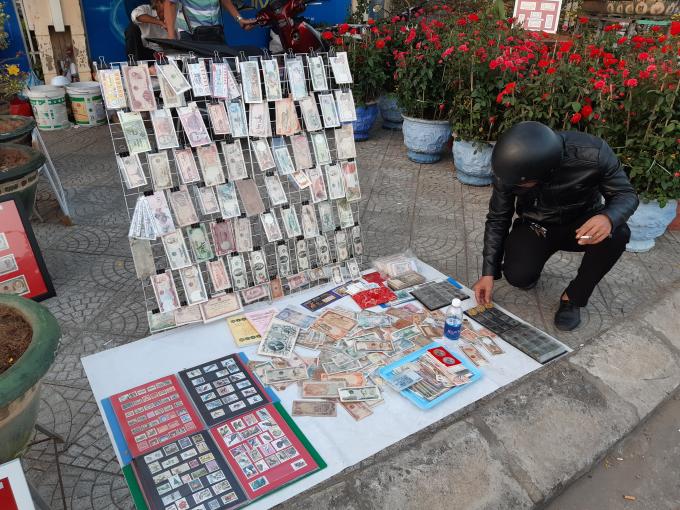 Du khách thích thú trước gian hàng bán tiền cổ và những đồng tiền nước ngoài được trưng bày dọc chợ Hoa tết.