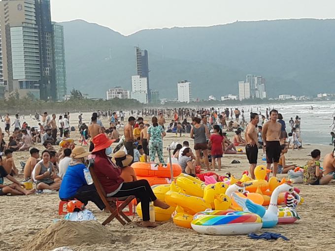 Chiều 1/5, người dân và du khách có mặt đông đảo tại bãi tắm trên đường Võ Nguyên Giáp, quận Sơn Trà, TP Đà Nẵng để nghỉ ngơi, du lịch trong 4 ngày nghỉ lễ.