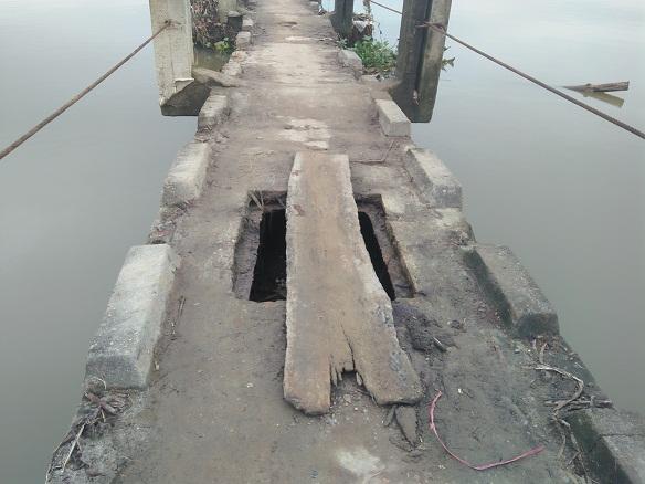 Ổ voi xuất hiện ngay trên mặt cầu, người dân lo sợ đến tính mạng nên lấy miếng gỗ vá lại.