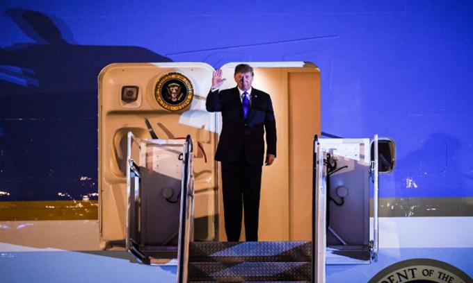Tổng thống Trump vẫy chào trên chuyên cơ Không lực Một khi tới sân bay Nội Bài tối 26/2. Ảnh:AFP.