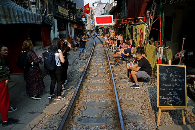 Hàng ngày, những quán cà phê sát đường tàu đoạn từ đầu phố Trần Phú đến phố Phùng Hưng đông nghẹt du khách ngồi uống cà phê đợi các đoàn tàu đi qua.