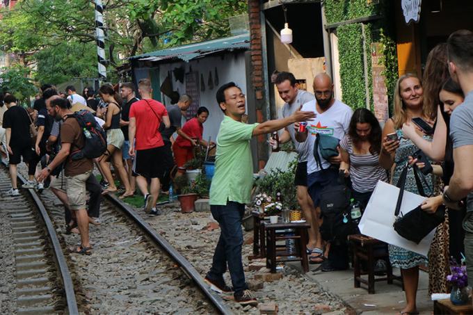 Mỗi khi có đoàn tàu sắp chạy qua, các chủ quán cà phê chạy đôn, chạy đáo nhắc nhở du khách đứng nép sát vào tường quán để tránh xảy ra tai nạn.
