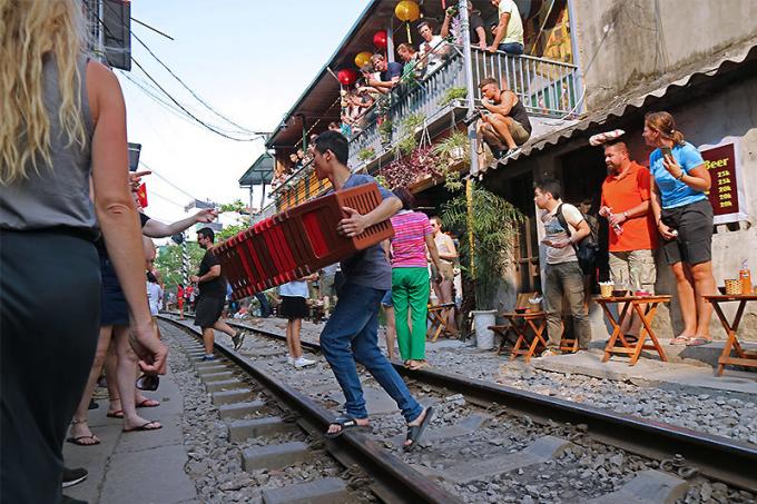 Bàn ghế được nhân viên các quán nhanh chóng thu dọn trước khi đoàn tàu chạy qua.