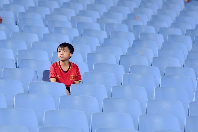 Một em nhỏ ngồi giữa những chiếc ghế trống để cổ vũ đội tuyển U23 Việt Nam thi đấu với đội tuyển Brunei.