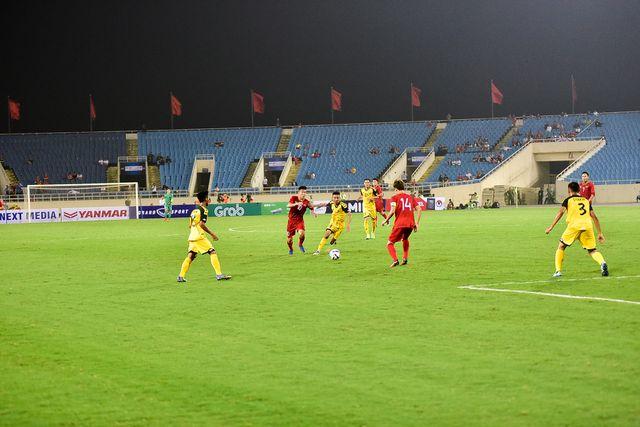 Ở góc máy này, chúng ta có thể thấy các cầu thủ đang thi đấu dưới sân, phía đằng xa trên khán đài có lác đác cổ động viên chủ yếu là nhiều ghế không có người ngồi.