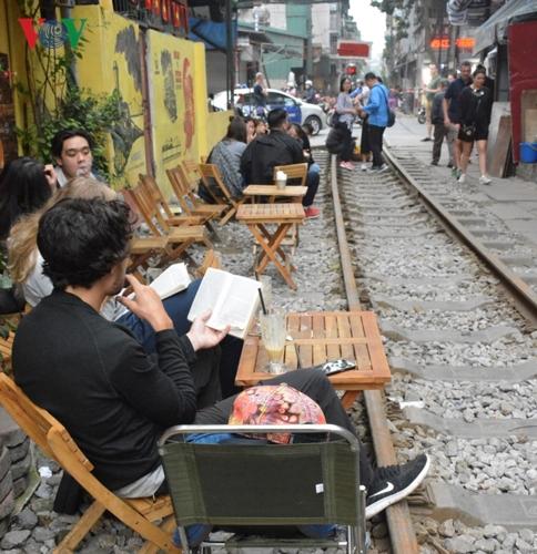 Họ thoải mái ngồi uống cà phê, nói chuyện vui vẻ ngay cạnh đường ray.