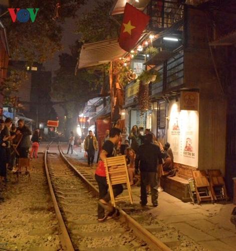 """Mỗi khi chuẩn bị có đoàn tàu chạy qua, chủ các quán cà phê này lại """"nháo nhào"""" thu dọn bàn ghế, hô hoán du khách nép sang hai bên đường tàu."""