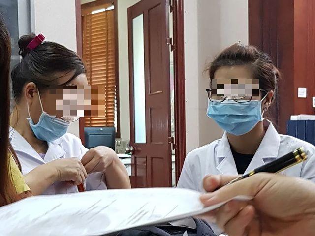 Chiếc khẩu trang luôn che trên mặt bác sĩ (bên phải) cùng nữ phiên dịch