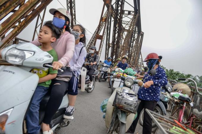 Dọc hai bên cầu có đến hơn chục điểm người dân họp chợ. Thỉnh thoảng những người chở hàng đến dừng đỗ, vận chuyển càng làm cho lối đi bị rối.